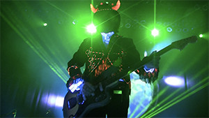 Simon Posford playing guitar with top hat and horns in green light silhouette