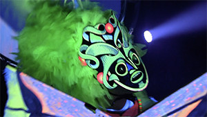 performer with neon green mask and wig on stage
