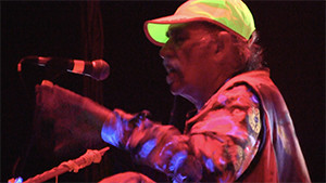 Raja Ram on stage with neon green hat