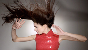 brunette fashion model hair blowing in the wind arms reaching