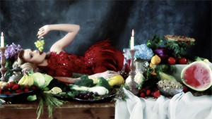 fashion model in studio wearing red dress laying on table surrounded by fruit