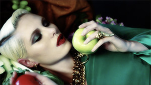 blond fashion model in studio laying on table eating apple