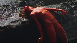 Kathi Von Koerber painted red laying on rock