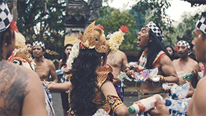 Balinese dance traditional costumes at temple holding plastic bottles