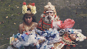 Balinese girl and father in traditional costumes and makeup carrying dead girl enveloped in plastic